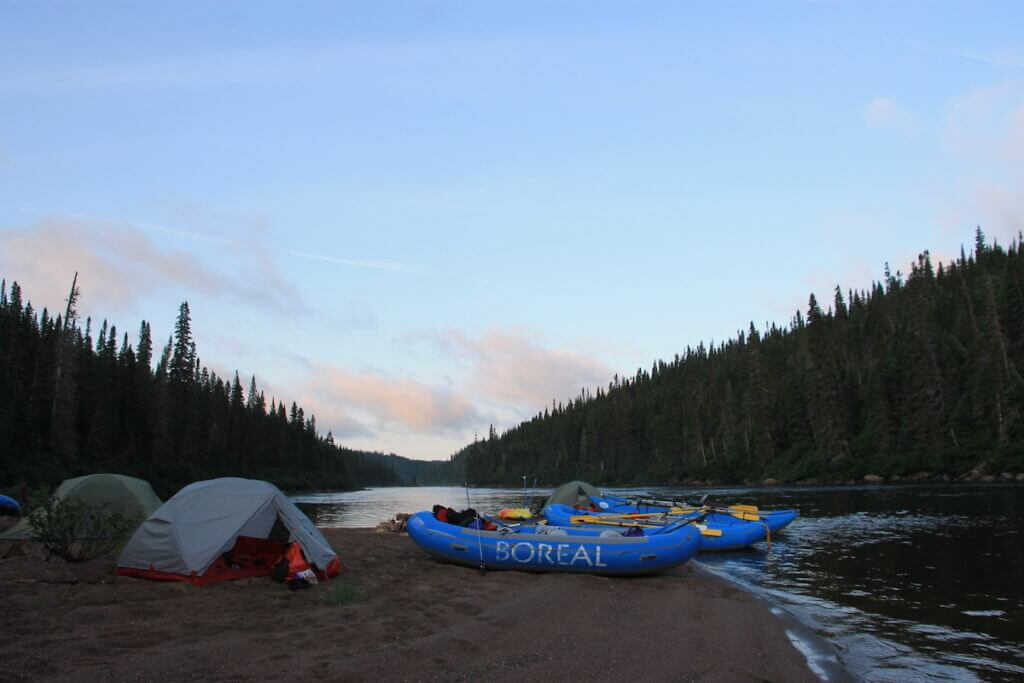 Rafts pulled up on shore next to the tents at camp