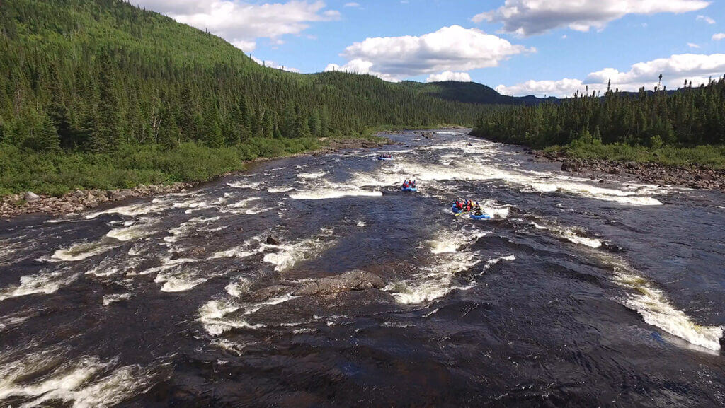 3 raft groups heading down a set of rapids all in a line in rafts