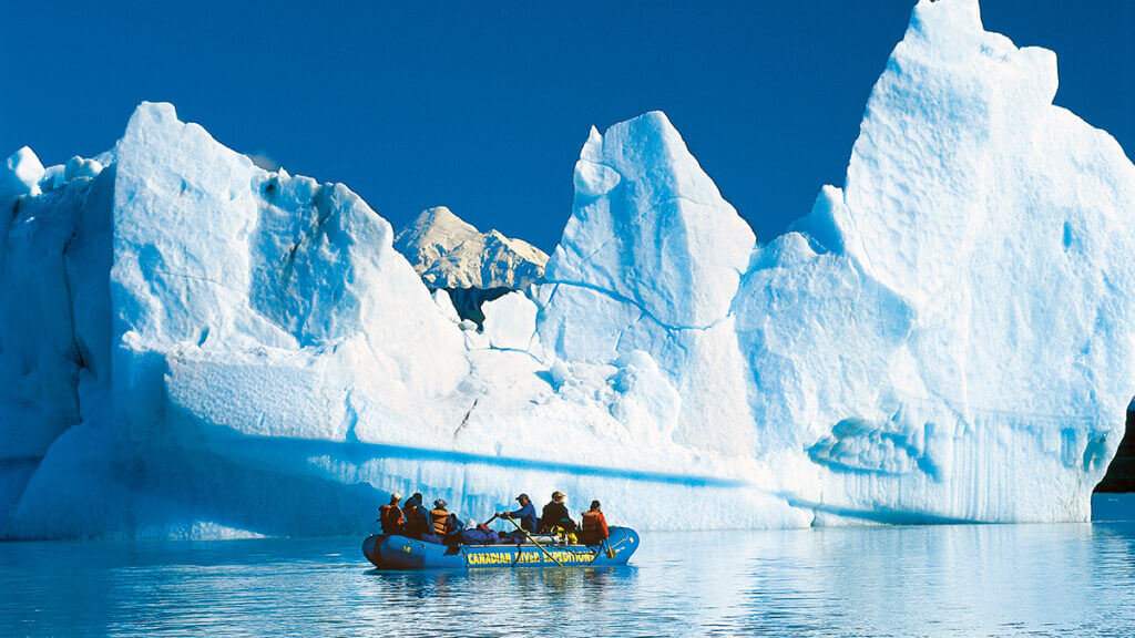 A group rafting next to icebergs on a lake in Northwestern British Columbia Canada. One of the best multi-day white water rafting trips in Canada.