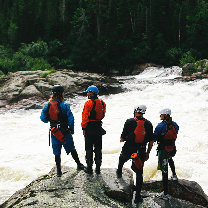 Group of Raft Guides Scouting A Set Of Rapids