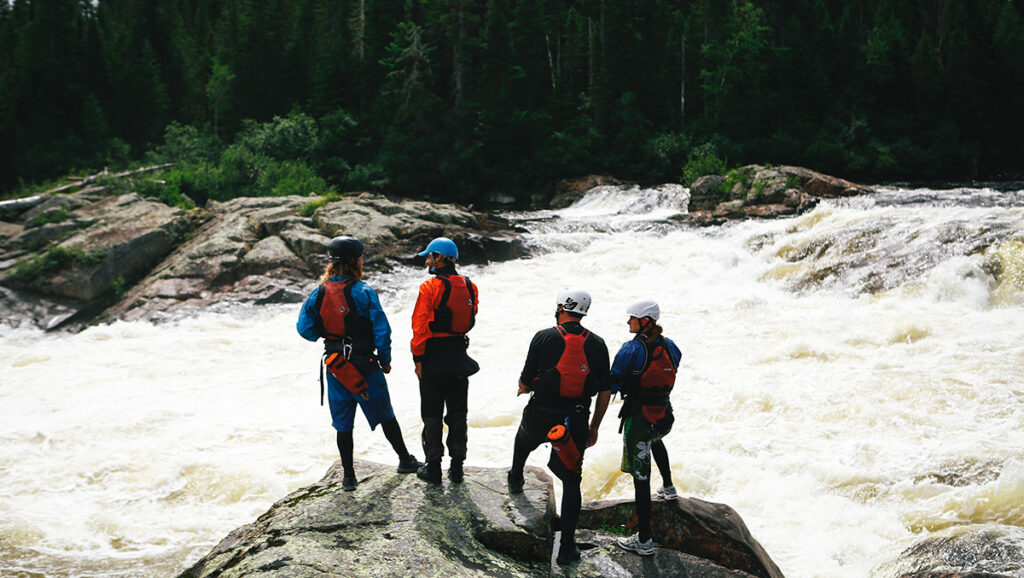 Raft guide and participants scouting a rapid